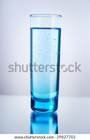 A glass of liquid on a reflective surface. Blue tint.