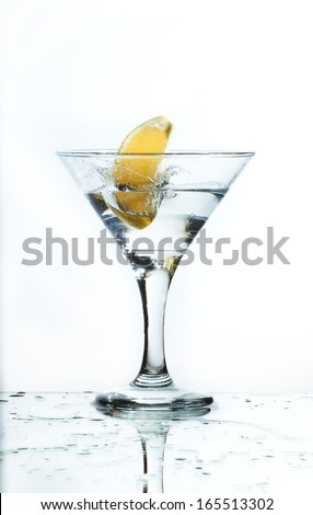 A glass of martini and slice of lemon, a splash and spray on a light background, selective focus