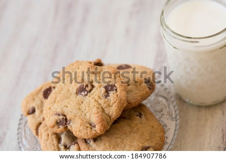 A glass of milk and a stack of chocolate chip cookies for dessert - stock photo