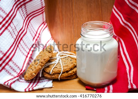 A glass of milk with oatmeal and raisins cookies in a rustic kitchen
