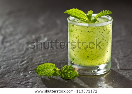 A glass of Mojito, a kind of cocktail drink on stone background - stock photo