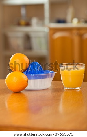a glass of orange juice, and a juicer on the table in the kitchen - stock photo