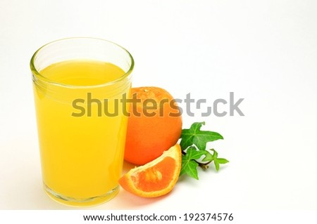 A glass of orange juice flanked by a whole and a wedge of orange. - stock photo