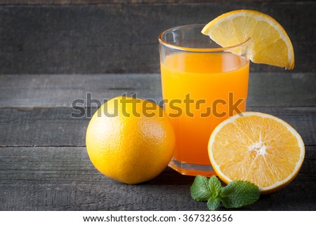 a Glass of orange juice, mint and slices of orange on wooden background. Healthy drink concept. Vitamines and diet. Shake and smoothie. - stock photo