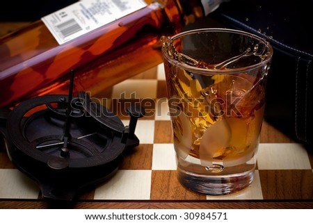 a glass of pure whiskey with ice and the bottle on background - stock photo