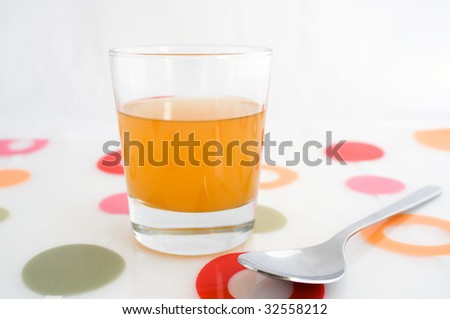 "A glass of raw, unfiltered apple cider vinegar, with ""mother"". - stock photo"