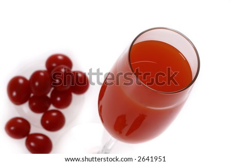 a glass of red drink with out-of-focused cherry tomatoes - stock photo