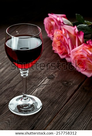 A glass of red wine and three roses on wooden background. - stock photo