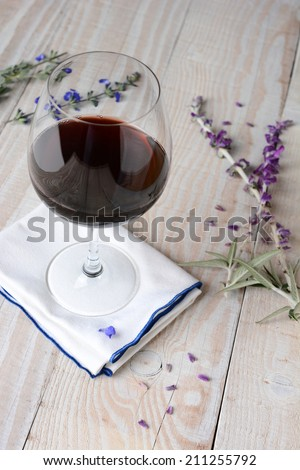 A glass of red wine on a napkin and a white rustic wood table. Flowers and petals are scattered on the table. Vertical format shot from a high angle. - stock photo