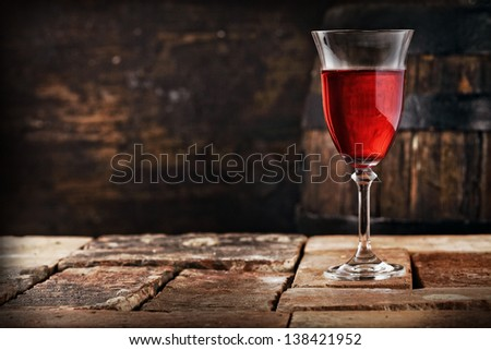 A glass of red wine on an old rustic table, shallow depth of field. - stock photo