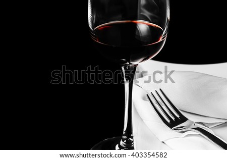 A glass of red wine, white plate with a fork and white napkin on black background