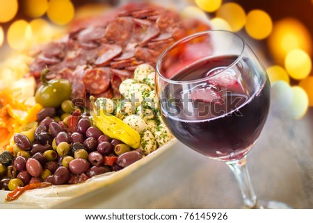A glass of red wine with a platter of Italian antipasto behind and festive lights. - stock photo