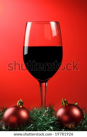 A glass of red wine with xmas decorations on a graduated red background. - stock photo