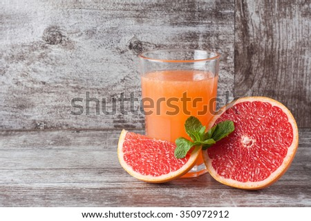 A glass of ripe grapefruit with juice on wooden table close-up - stock photo