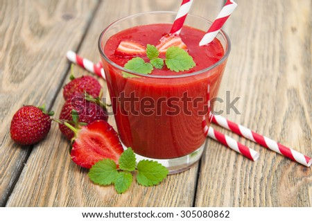 A glass of strawberry smoothie on a wooden background - stock photo