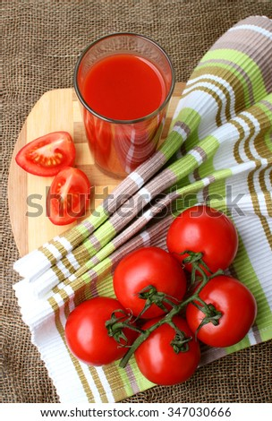 A glass of tomato juice and ripe tomatoes.