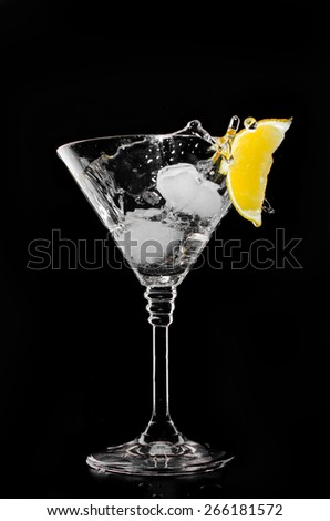 A glass of vermouth with ice and a slice of lemon. On a black background. - stock photo
