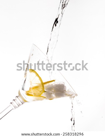 A glass of vermouth with ice cubes and lemon slices with water