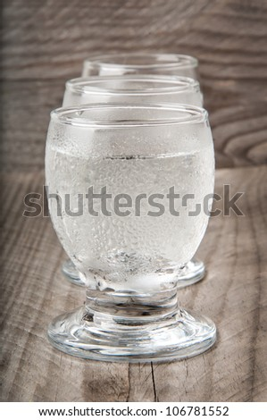 a glass of vodka on a wooden background