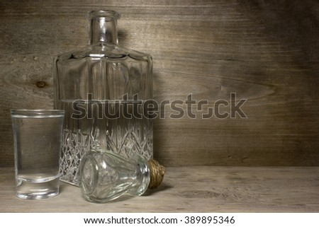 A glass of vodka on wooden table.