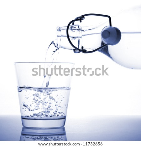 A glass of water being poured from a bottle. - stock photo