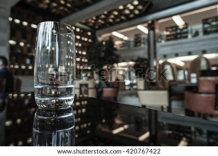 A glass of water on the table in lounge bar background.