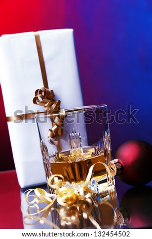 a glass of whiskey against two colored background christmas gift box and red ball decoration - stock photo