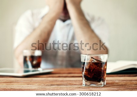 A glass of whiskey with cola on a wooden table. Against the background of men hands cover their faces. Concept of alcoholism. Copy space. Free space for text. Closeup - stock photo