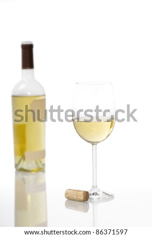 A glass of white wine and cork with the open bottle out of focus in the background on a white background.  Reflections prominent in image.  Plenty of copy space.