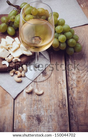A glass of white wine, grapes, cashew nuts and soft cheese on a wooden board, rustic style background - stock photo