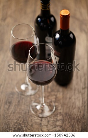A glass of wine and few wine bottles on the wooden background - stock photo