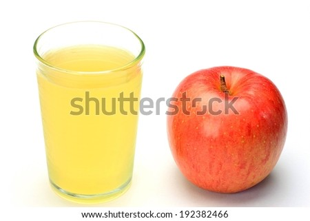 A glass of yellow liquid next to a red apple. - stock photo