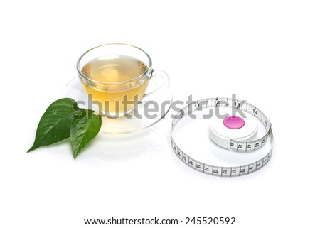 A glass tea cup with tape measure, leaf isolated white at the studio. - stock photo
