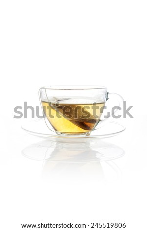 A glass tea cup with tea bag isolated white at the studio. - stock photo