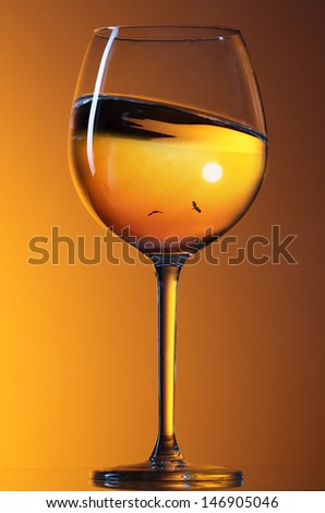 a glass with a drink and a reflection of the sun and birds - stock photo