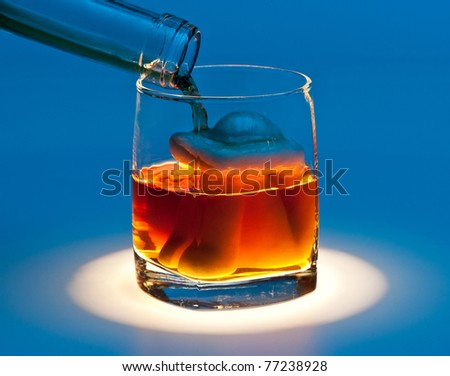A glass with a woman figure inside and an alcoholic drink flowing in, blue background - stock photo