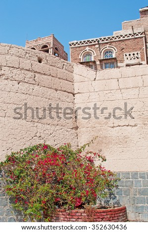 A glimpse of a decorated house behind a wall in the Old City of Sana'a, Republic of Yemen, Unesco world heritage site with unique architectural characteristics - stock photo