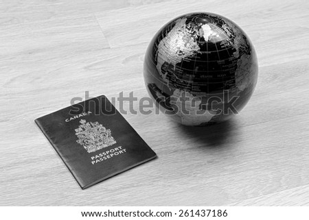 A globe next to a passport on a wood floor in black and white - stock photo