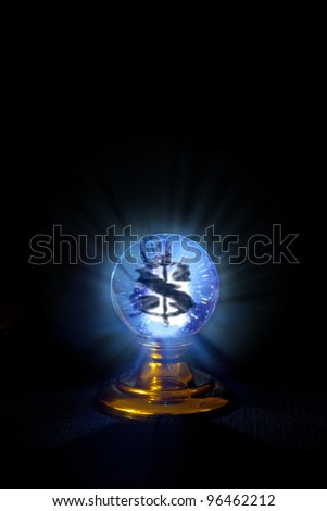 A glowing crystal ball sits on black with a vision of a dollar sign within it. - stock photo