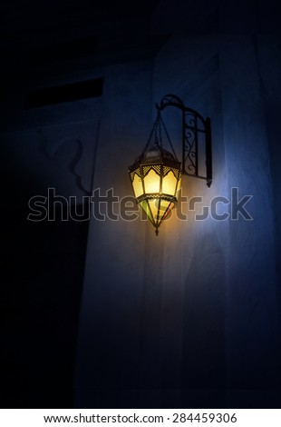 A glowing turkish wall mounted lamp in the dark. - stock photo