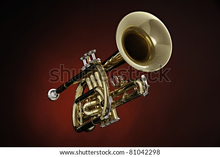 A gold brass cornet or trumpet isolated against a spotlight red background - stock photo