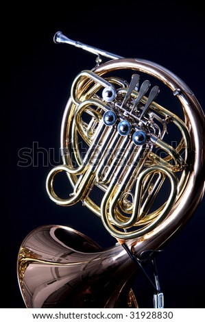 A gold brass French  Horn isolated on a black background in the vertical format with  copy space. - stock photo