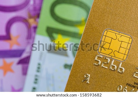 a gold credit card and euro banknotes. symbolic photo for cashless transactions and status symbols. - stock photo