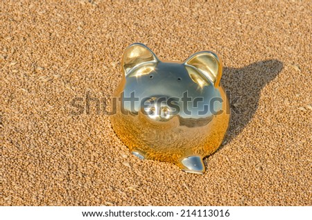 A gold piggy bank in a pile of wheat - stock photo