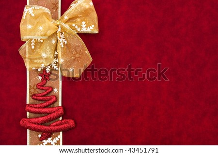 A gold ribbon bow sitting with a snowflake ribbon on a red background
