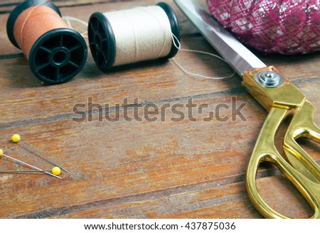 A gold scissors and spool of thread with pins