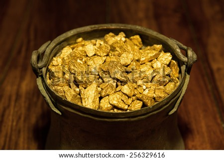 a Gold treasure in a copper kettle - stock photo