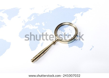 A gold vintage(classic, old) magnifier(reading glass) focus in indonesia on the blue world map. - stock photo