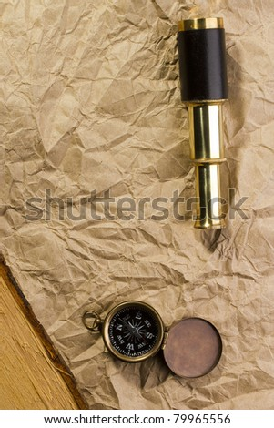 A golden compass and a spyglass laying on an old wrinkled brown paper that can serve as a background for a message or a drawing of a map.