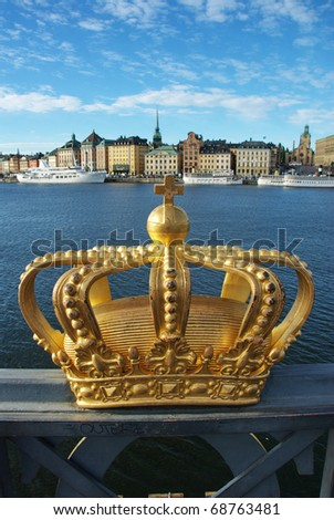 A golden crown on Skeppsholmen bridge with Royal palace in the background